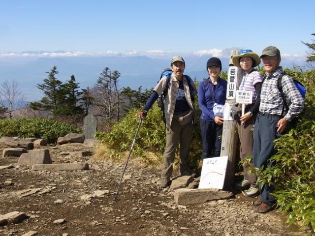 08岩菅山頂で記念写真(遠く北アルプスが見える)