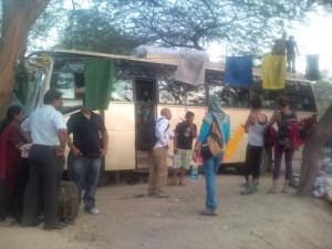 壊れたバスを囲む人々