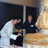 大日如来坐像にノミを入れるブータン国王夫妻(左と中央、京都市中京区で)