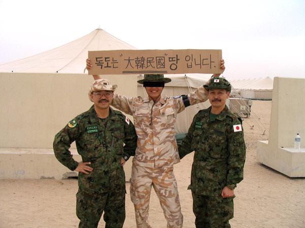陸自隊員の背後で「独島は韓国領」というプラカードを掲げてバカにする韓国人