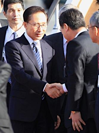 大阪空港に到着し、出迎えた関係者と握手する韓国の李明博大統領=17日午後