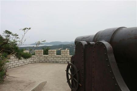 旅順港を臨む「28サンチ榴弾砲」の砲身はゴミが散乱していた=中国・旅順