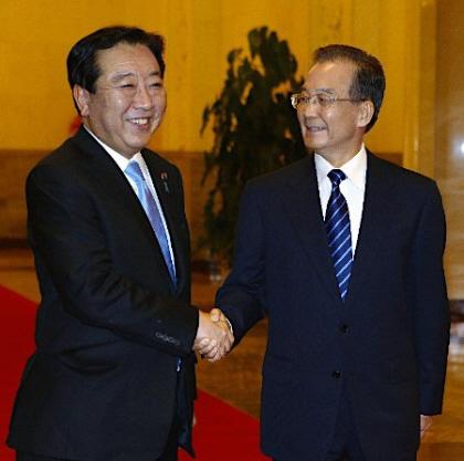 野田佳彦首相は25日午後(日本時間同)、中国公式訪問のため政府専用機で北京入りし、人民大会堂で温家宝首相と会談した。写真は歓迎式典を前に出迎えた温首相(右)と笑顔で握手する野田首相