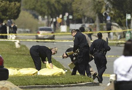 オイコス大学の銃撃事件で、遺体に覆いをかける警察官=2日、オークランド(AP)