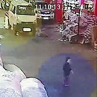 女児(右手前)が白い車にひかれる直前の状況をとらえた防犯カメラの映像(13日、AP)
