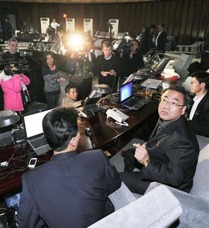平壌市内のプレスセンターで、人工衛星と主張する長距離弾道ミサイルを発射したとの報道に、対応に追われる北朝鮮の関係者ら(手前)=13日午前8時20分