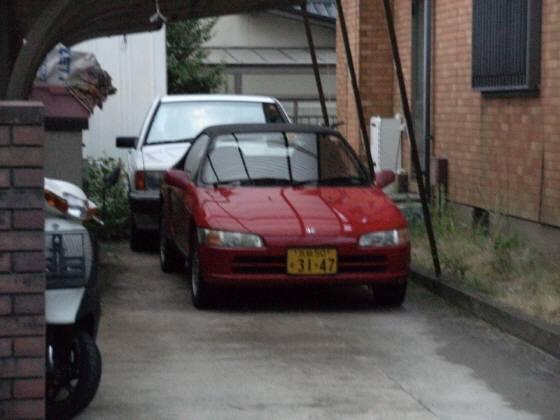 ベンツ、真っ赤な高級スーパーカー(フェラーリ?)、ワゴン車が3台並ぶ。