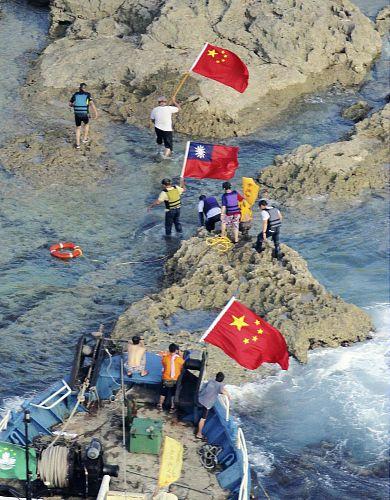 支那の国旗などを手に魚釣島に上陸する香港の民間団体の活動家ら(15日午後5時35分)