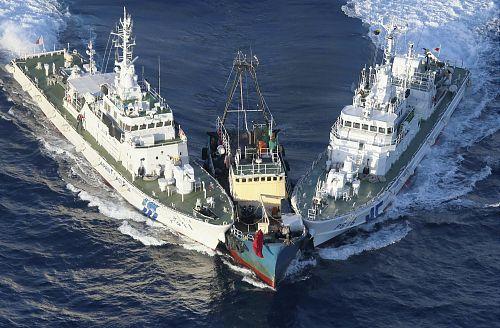 活動家らを島に降ろした後、魚釣島沖で海上保安庁の巡視船に挟まれる支那の犯罪船(中央)(15日午後6時46分)