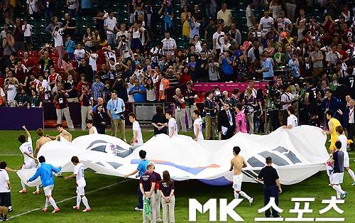 「独島は我々の領土」と書いた紙を韓国国旗の上に載せて韓国チームの皆が運んでる画像