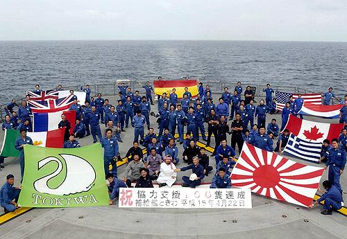 インド洋補給終了 海自の実力示した 洋上補給100隻を達成、給油した各国の旗を並べ記念写真に収まる補給艦「ときわ」乗員(2003年4月22日)