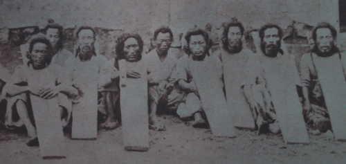 首枷をした囚人たち(首の部分だけ穴の開いた板を着装している)