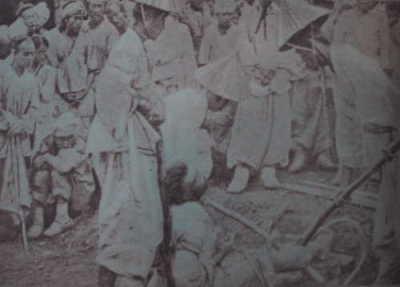 チュリの刑を受ける囚人(両脚の間に二本の棒を差し込んでいる)