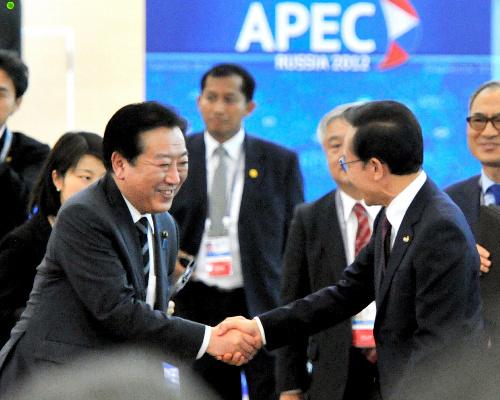APEC首脳会議を前に韓国の李明博大統領(右)と握手する野田佳彦首相。アルファベット順の席次のため、隣同士になった=8日午後3時37分、ロシア・ウラジオストク、仙波理撮影
