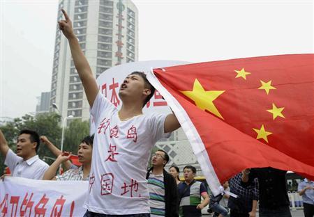 11日、北京の日本大使館前で中国国旗を掲げる男性(共同)