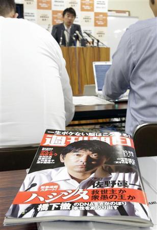 橋下徹大阪市長の出自を題材にした記事が掲載された週刊朝日。奥は記事について発言する橋下市長=18日午後、大阪市役所 週刊朝日が連載打ち切り 「不適切な記述が複数あった」