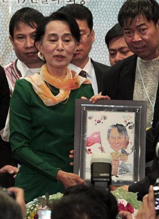 金大中元大統領の記念図書館でスピーチし、終了後に記念品を手にするアウン・サン・スー・チー氏=1日、ソウル(AP)