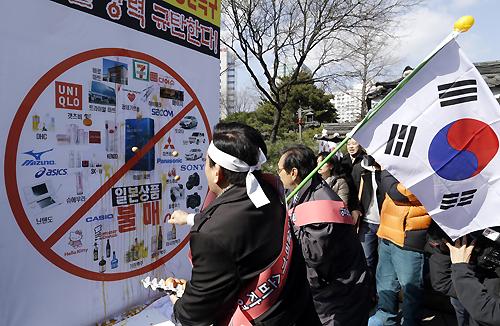 日本製品の写真に生卵を投げる人々