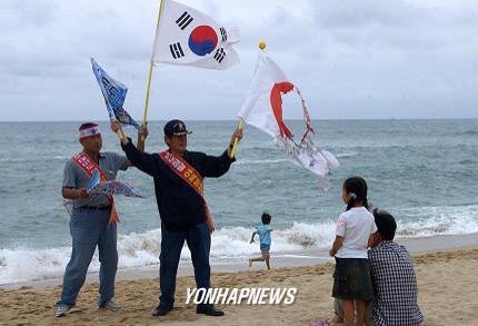 対馬での韓国人旅行者による愚かな行為。日章旗を破り、太極旗を掲げ、韓国の領土だとアピールする醜い韓国人旅行者。