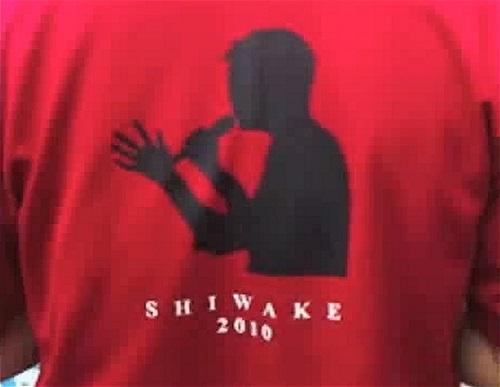 東京・JR新橋駅前広場で準備にあたるスタッフ。のぼりとおそろいの深紅のシャツを着て堂々と活動