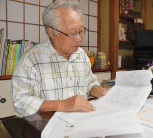 署名に添えられた手紙に目を通す石垣義昭さん=相模原市で