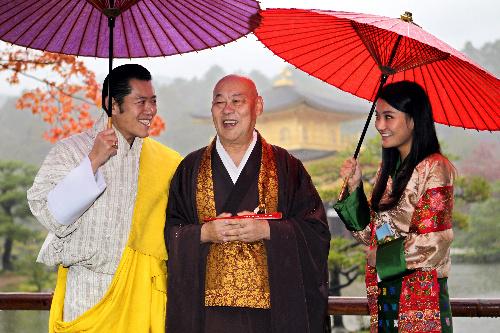 報道陣の写真撮影に応じる際、金閣寺の有馬住職(中央)を気遣い、傘を差し掛けるブータンのワンチュク国王(左)とジェツン・ペマ王妃