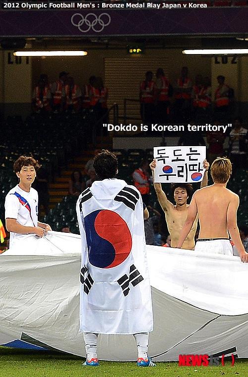 大韓民国が日本に2:0で完勝して銅メダルを確定し、選手たちが大型太極旗を持って「独島(ドクト)は私たちの土地」プラカードを持ち上げて見せている。