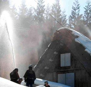 合掌家屋で放水訓練をする消防団員ら=白川村荻町で