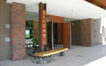 欅の看板とカバ材のベンチがあるエントランス