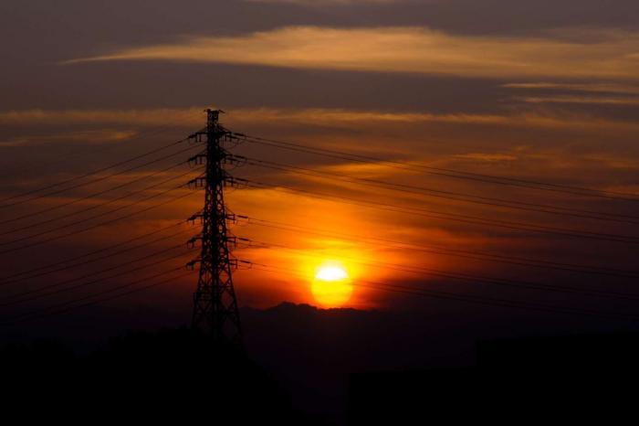 高圧線の向こう側に沈む夕日