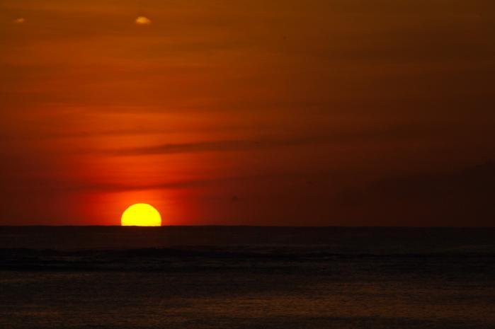 水平線に沈む真っ赤な太陽と夕焼け