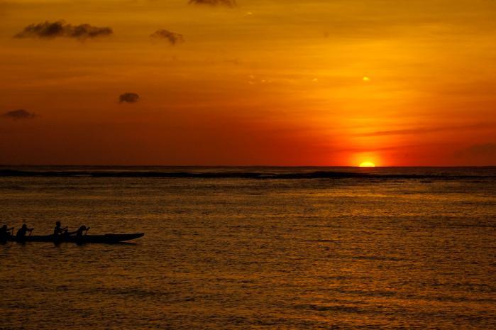 水平線に沈む真っ赤な太陽とカヌー(カヤック)