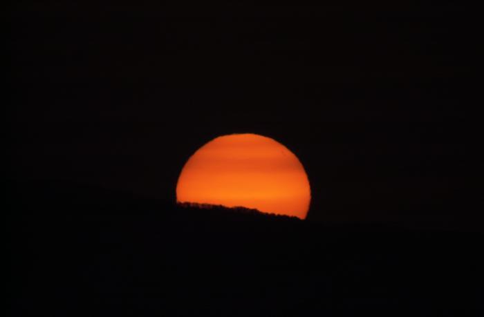 オレンジ色の太陽に縞模様が見える(日の出)