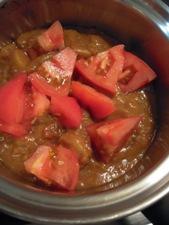 カレーにトマトと水を加えて煮込みます