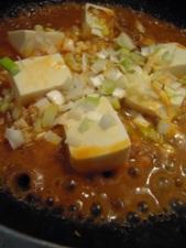 豆腐とねぎを加えて煮込みます