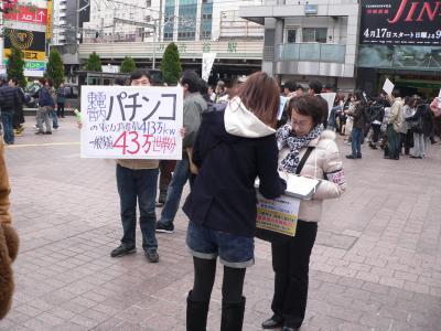 写真キャプション=節電を呼びかるプラカードの横で署名する女性