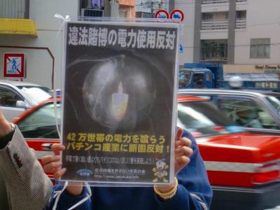 写真キャプション=ポスターを掲げてパチンコ店の営業停止を訴える会員