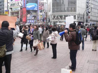 """写真キャプション=多くの顧客で賑わうホールがある一方、渋谷の駅前で行なわれた""""節電署名""""の運動"""