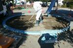 砂場の表面をレーキで掻き集める